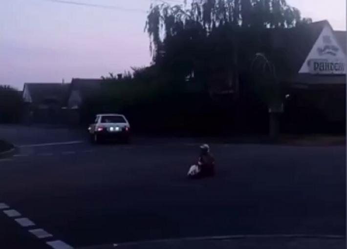 В Мелитополе женщина сидит на проезжей части и бросается под авто (видео)